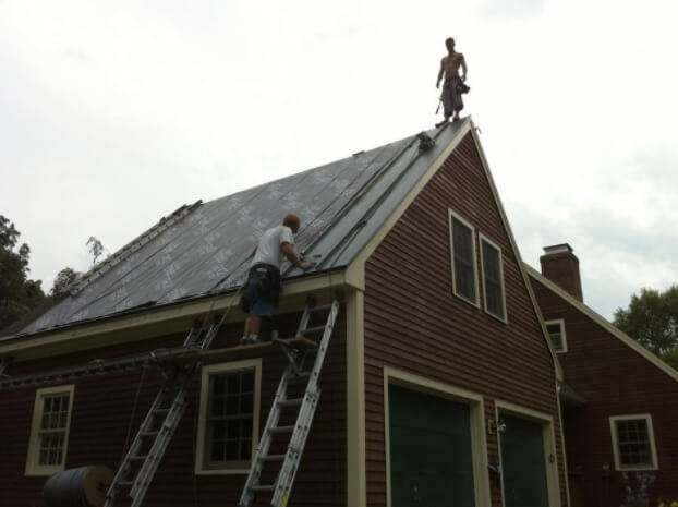 Two workers roofing a house