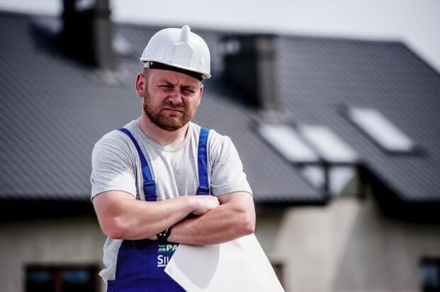 A contractor with arms folded, holding plans, standing in front of a new roof