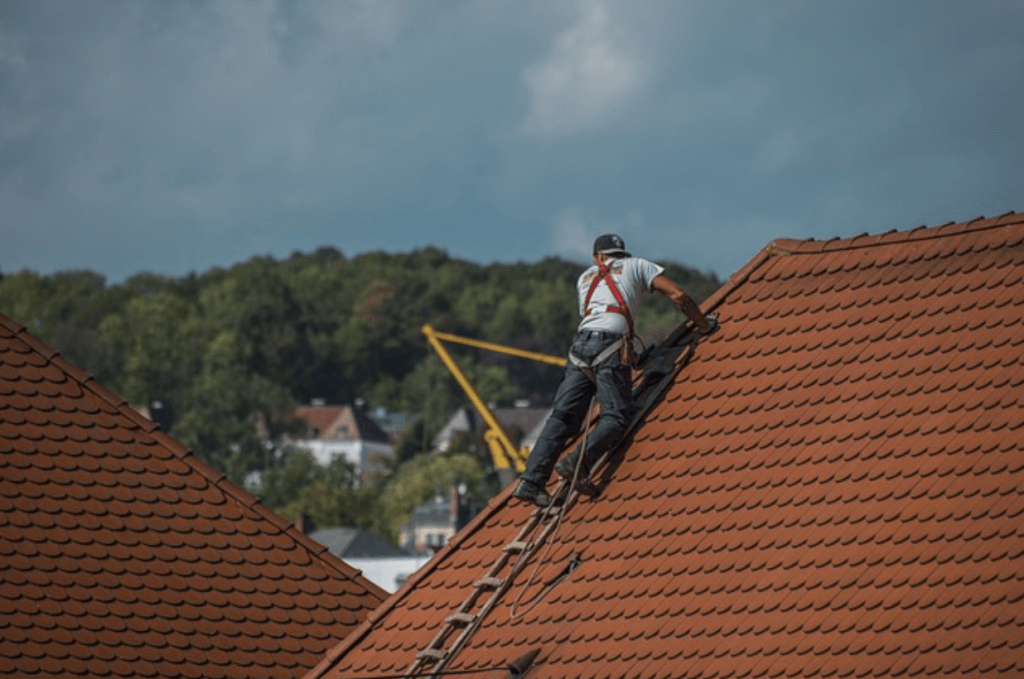 A roofer working to maintain a tile roof
