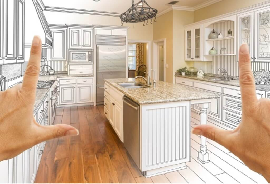 A person framing a kitchen between their fingers, planning a new home addition