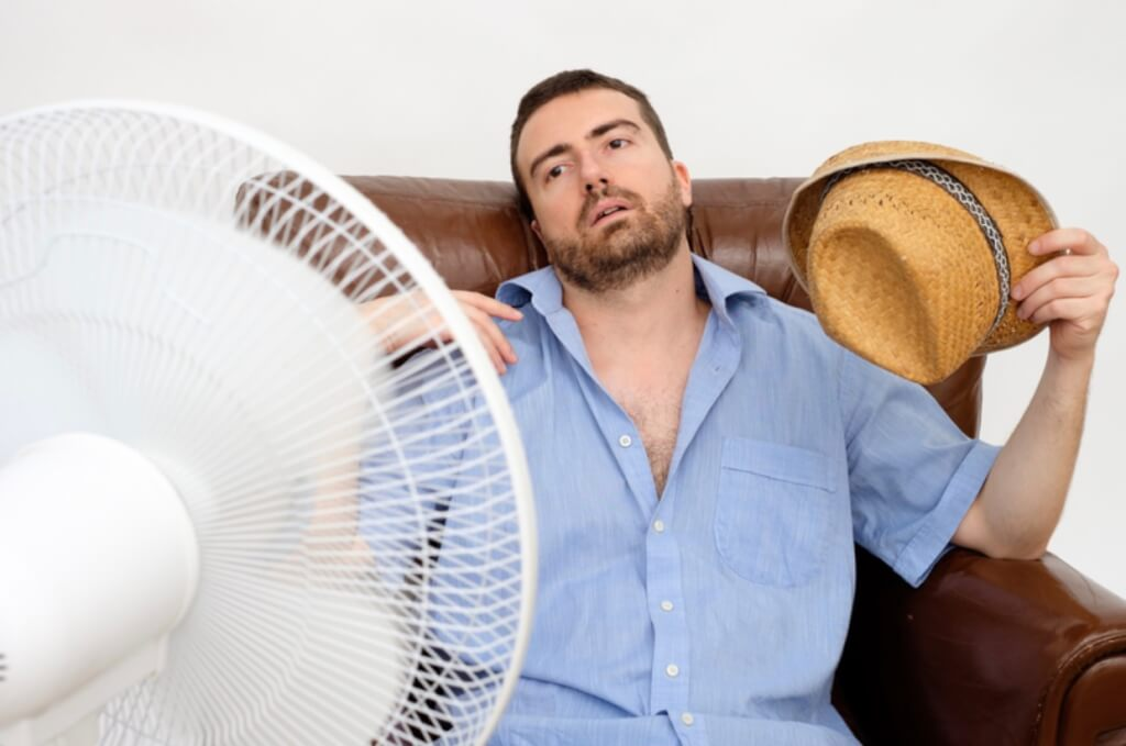 Man sitting in front of fan, trying to cool down.