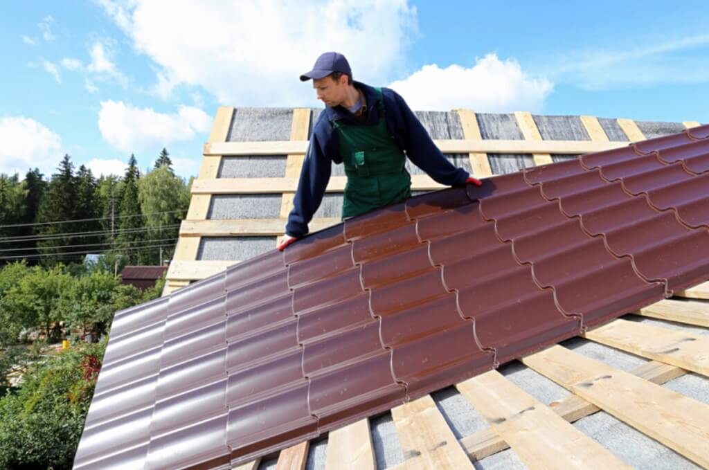 Roofer installing long metal roofing panels