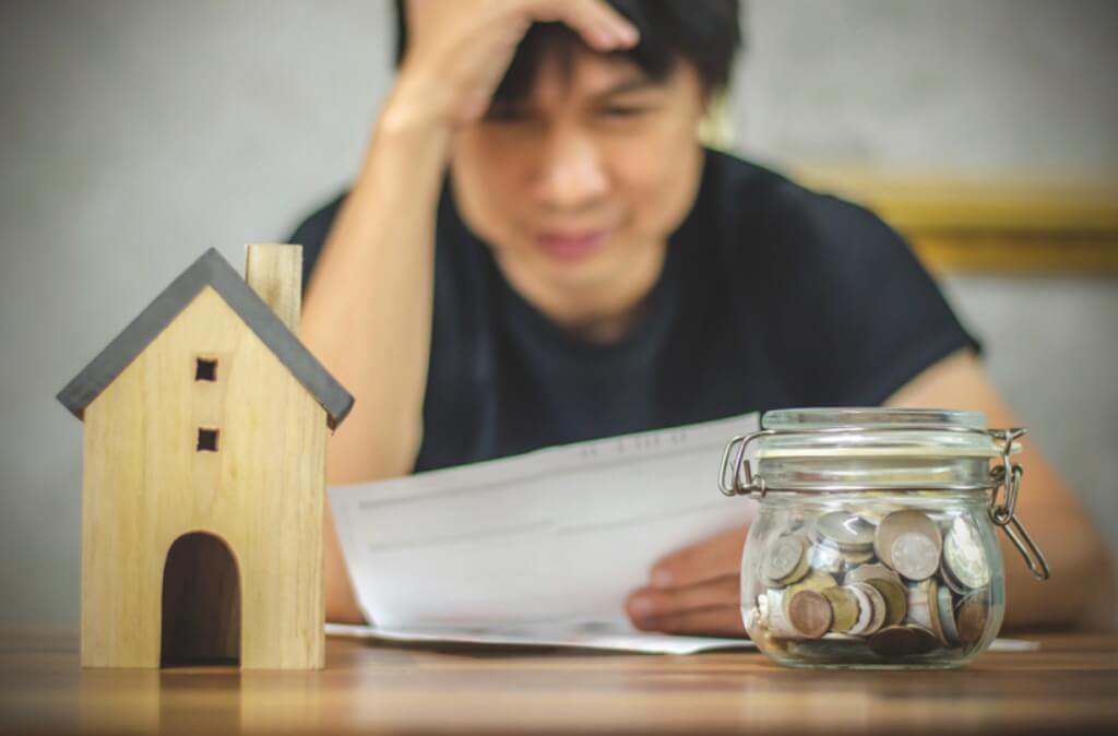 Man looking at jar of money